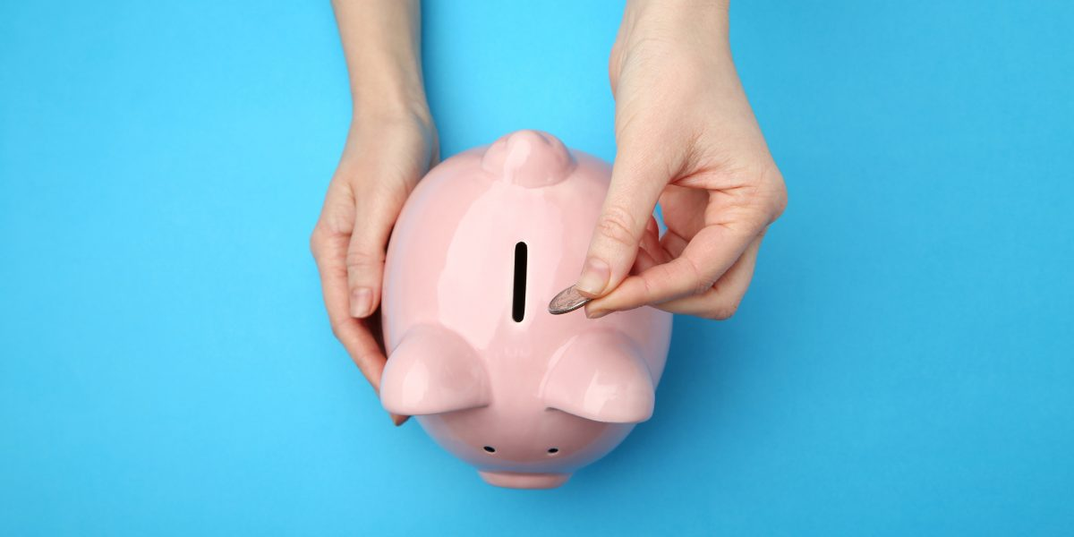 Female hand putting coin into piggy bank on blue background