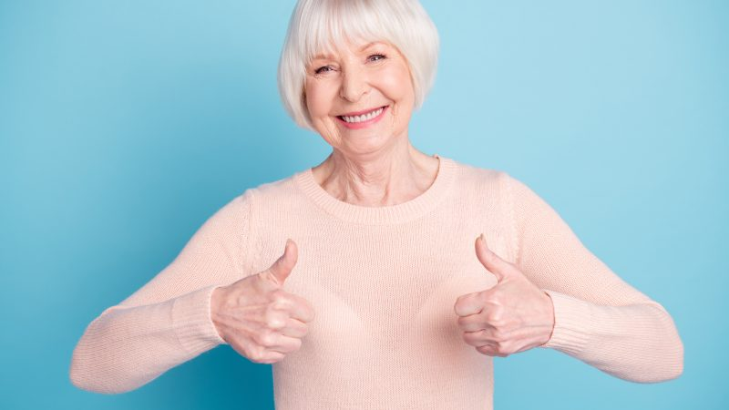 Portrait of cheerful lady showing, thumb up smiling wearing paste jumper isolated over blue background