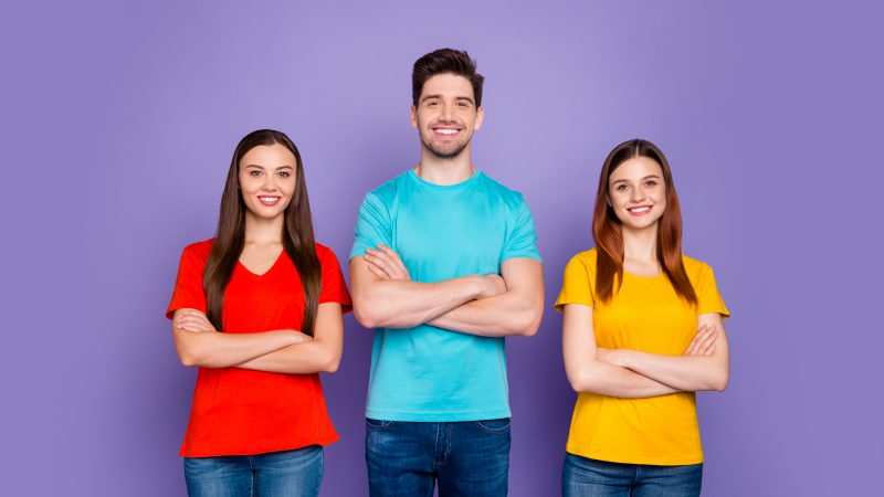 Portrait of nice attractive lovely charming cheerful cheery content guys wearing, colorful t-shirts jeans denim crossed hands active social position isolated over violet lilac background