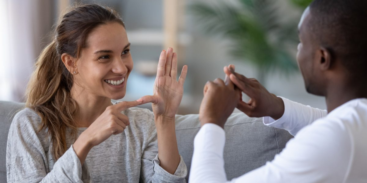 Smiling mixed ethnicity couple or interracial friends talking with sign finger hand language, happy two deaf and mute hearing impaired people communicating at home sit on sofa showing hand gestures